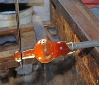 Glass blower from Mexico blowing a red rim wine glass