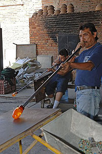 Two artisans are blowing in the tubes to make the hot glass shapes larger to work with